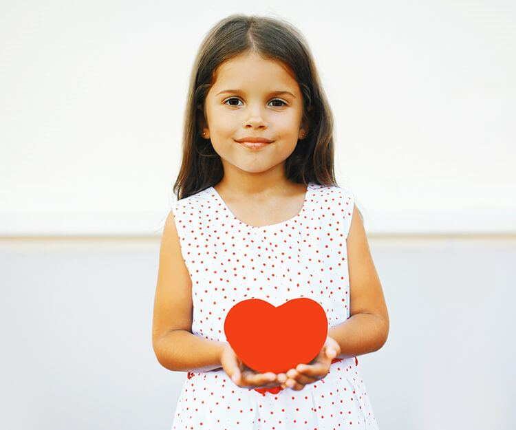 Little girl with a heart in her hands