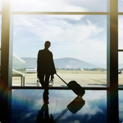 Uma pessoa olhando através da janela do terminal com um saco de transporte